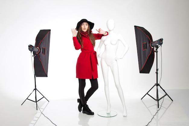 Mooi interessant meisje in de hoed naast de witte vrouwelijke etalagepop poseren in studio op witte achtergrond