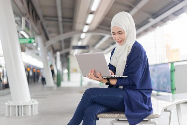 Mooi jong aziatisch meisje dat bij een skytrain met laptop werkt. moslimvrouwen