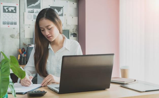 Mooi jong aziatisch meisje dat op een huiskantoor met laptop werkt