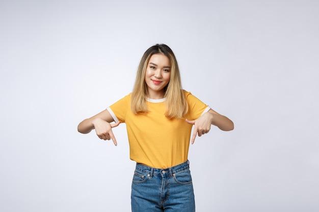 Mooi jong aziatisch vrouwenpunt neer aan lege ruimte op grijze achtergrond.