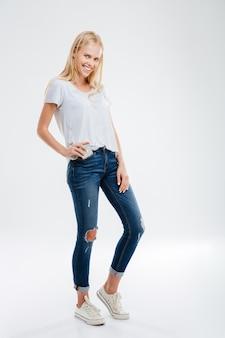 Mooi jong blond meisje dat smartphone in de jeanszak steekt die op een witte muur is geïsoleerd