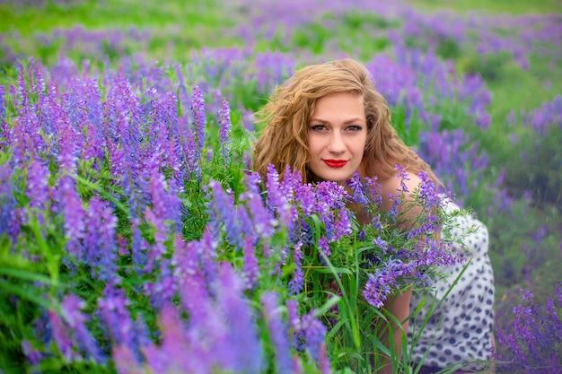 Mooi jong blond meisje in een groen veld tussen paarse wilde bloemen. wildlife mooi meisje.