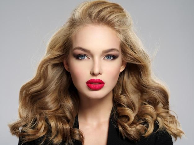 Mooi jong blond meisje met sexy rode lippen. close-up aantrekkelijk sensueel gezicht van blanke vrouw met lang haar. rokerige oogmake-up