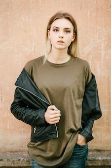 Mooi jong blondemeisje in een leeg groen t-shirt en leerjasje