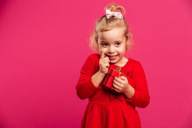 Mooi jong blondemeisje in rode kleding die idee hebben