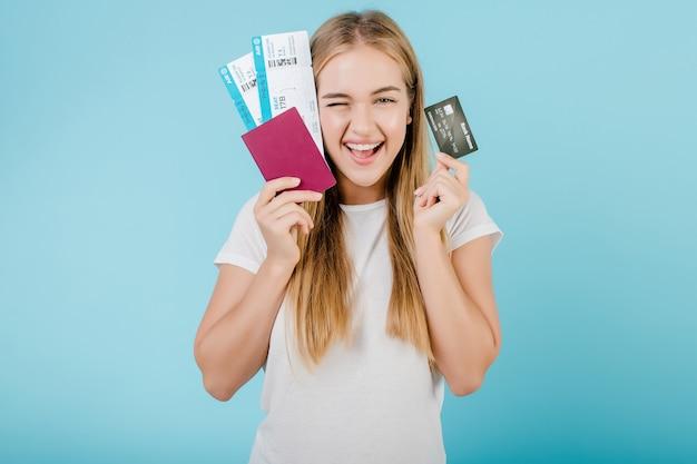 Mooi jong blondemeisje met paspoort en creditcard dat over blauw wordt geïsoleerd