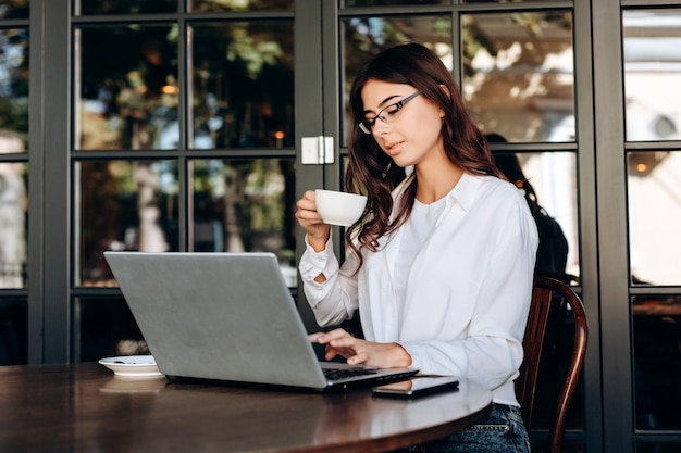 Mooi, jong brunette in glazen die koffie drinken en aan computer werken