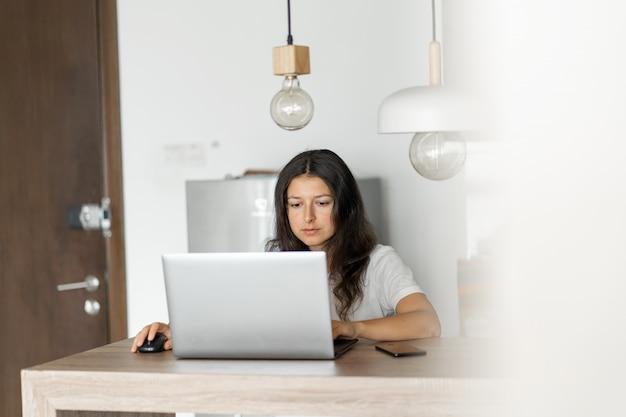 Mooi jong donkerbruin meisje die aan laptop thuis in de keuken werken.