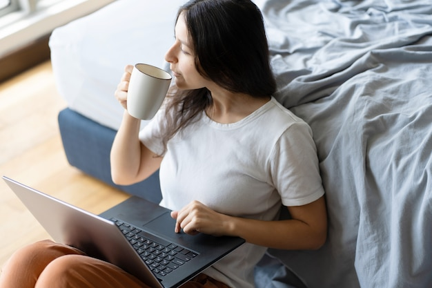 Mooi jong donkerbruin meisje die aan laptop werken en koffie drinken, zittend op de vloer dichtbij het bed door het panoramische venster met een prachtig uitzicht vanaf de hoge verdieping. stijlvol modern interieur