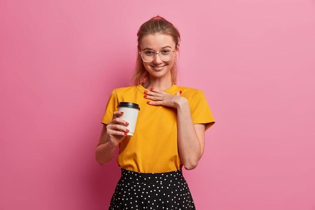Mooi jong europees meisje giechelt positief, proost over iets, drinkt afhaalkoffie, lacht van tevredenheid, heeft plezier in vrolijk gezelschap