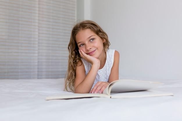 Mooi jong geitjemeisje die een boek op bed lezen en aan het venster kijken. familie liefde en levensstijl binnenshuis. dag