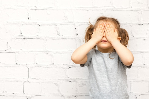 Mooi jong geitjemeisje die ogen behandelen voor verrassing dat over witte bakstenen muur wordt geïsoleerd