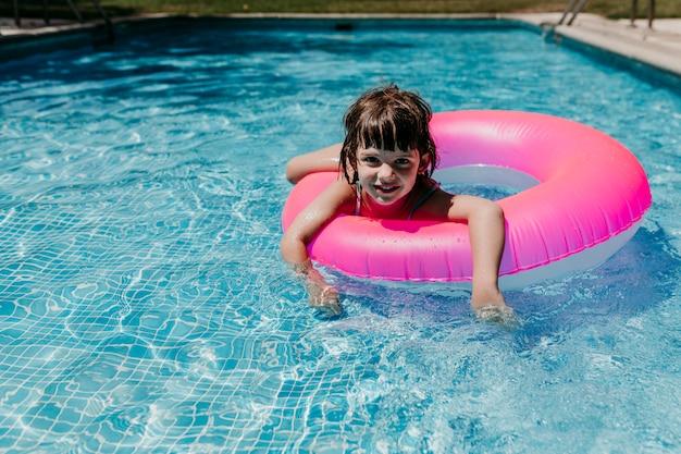 Mooi jong geitjemeisje die op roze donuts in een pool drijven. een zonnebril dragen en glimlachen. plezier en zomer levensstijl