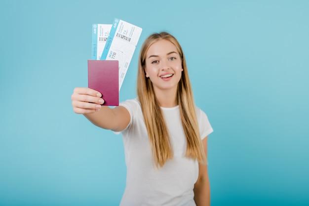 Mooi jong glimlachend blondemeisje met paspoort en vliegtuigkaartjes dat over blauw wordt geïsoleerd
