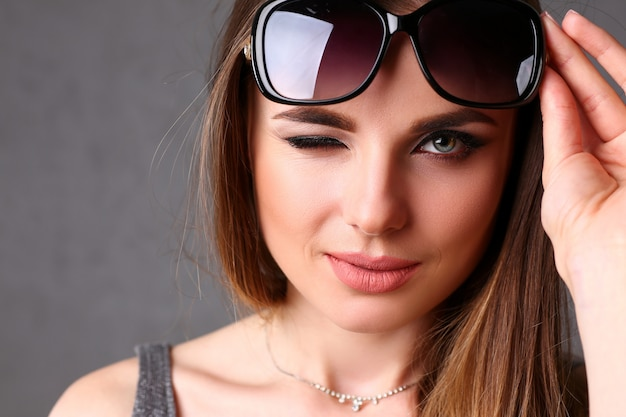 Mooi jong glimlachend donkerbruin meisje dat zonnebril draagt