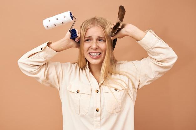 Mooi jong kaukasisch model in gekleurde borrels en wit overhemd en het stellen holdingskraanbalk in haar handen