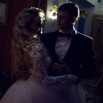 Mooi jong koppel, de bruid en bruidegom. luxe interieur. donkere, intieme sfeer