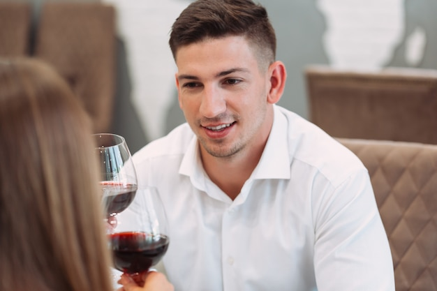 Mooi jong koppel met glazen rode wijn in luxerestaurant