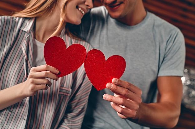 Mooi jong koppel thuis. verliefde paar harten in hun handen houden, knuffelen, zoenen en genieten van tijd samen doorbrengen tijdens het vieren van sint-valentijnsdag.