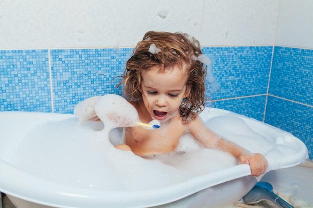 Mooi jong meisje baadt in de badkamer en borstelt haar tanden met een tandenborstel.