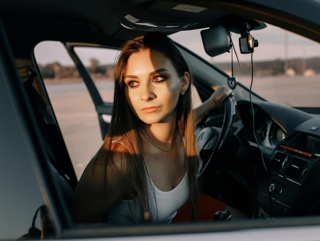 Mooi jong meisje besturen van een auto in de avond in de zonsondergangzon op een lege parkeerplaats