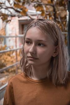Mooi jong meisje, blond, staat tegen de achtergrond van de herfstbladeren en struiken, met natuurlijk licht bij bewolkt weer.