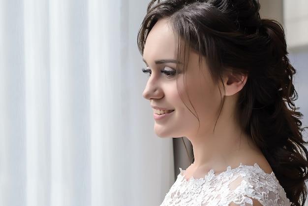 Mooi jong meisje bruid in een witte jurk permanent in hotelkamer en kijkt uit het raam