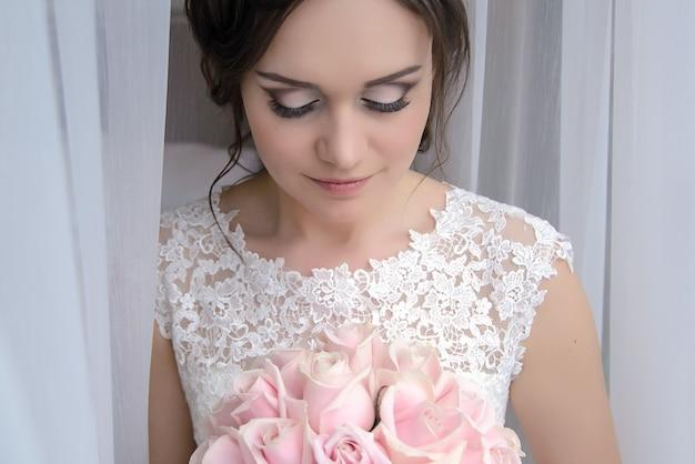 Mooi jong meisje bruid in een witte jurk staat achter een transparant gordijn bij het raam