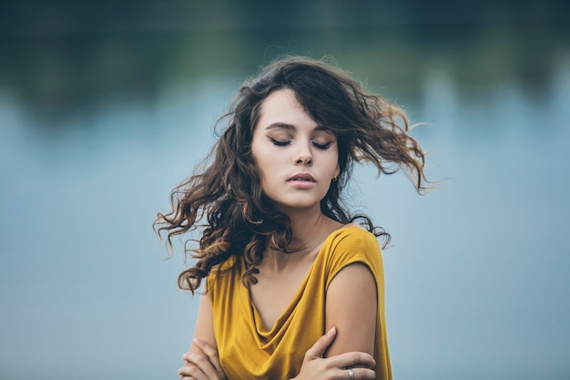 Mooi jong meisje close-up portret op de achtergrond van water in een lichte jurk