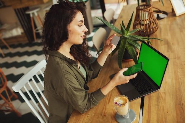 Mooi jong meisje dat bij een koffiewinkel werkt met een laptopvrouwelijke freelancer die een telefoon houdt