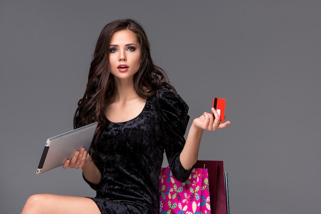 Mooi jong meisje dat door creditcard om te winkelen betaalt