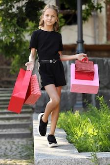 Mooi jong meisje dat door de stad loopt met gekleurde tassen