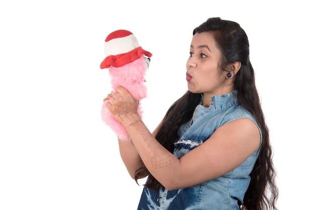Mooi jong meisje dat en met een teddybeerstuk speelgoed op een wit houdt speelt.