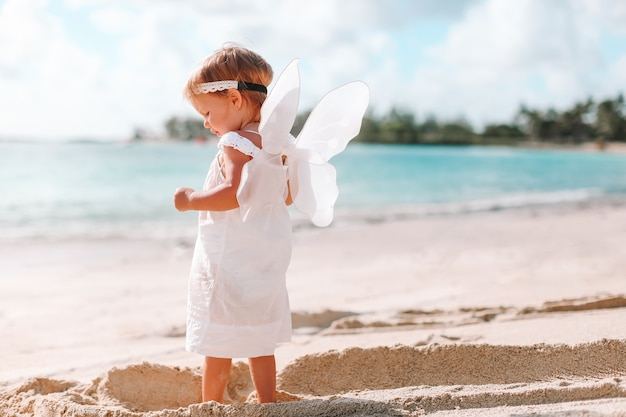 Mooi jong meisje dat engelenvleugels op het strand draagt
