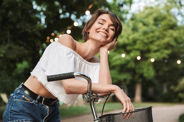 Mooi jong meisje dat in de zomerkleren op een fiets zit