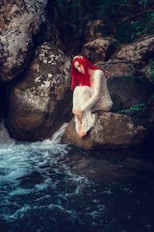 Mooi jong meisje dat in water rust. jonge vrouw in de witte jurk zit op de steen midden in een kreek.