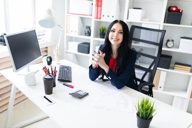 Mooi jong meisje dat met calculator en documenten in het bureau bij de lijst werkt