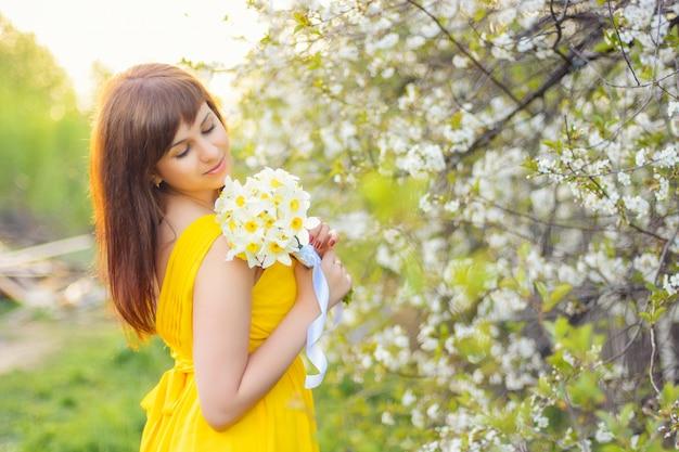 Mooi jong meisje dat met een boeket van bloemen in openlucht in de lente glimlacht