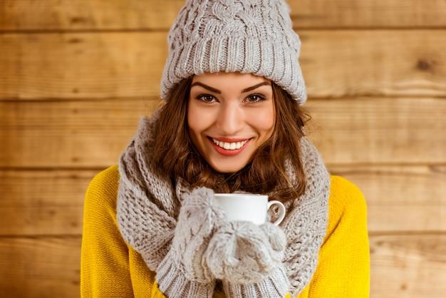 Mooi jong meisje dat met glb en handschoenen thee drinkt.