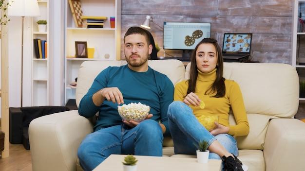 Mooi jong meisje dat op de schouder van haar vriendje ligt terwijl ze tv kijkt en chips eet. vriend die popcorn eet.