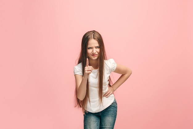 Mooi jong meisje dat op roze studiomuur wordt geïsoleerd