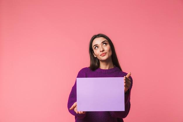 Mooi jong meisje dat sweater draagt die zich geïsoleerd over roze bevindt, leeg bord toont
