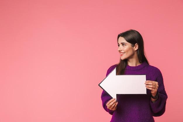 Mooi jong meisje dat sweater draagt die zich geïsoleerd over roze bevindt, met een pijl weg bij exemplaarruimte richt