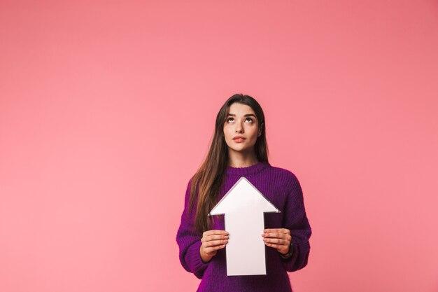 Mooi jong meisje dat trui draagt die zich geïsoleerd over roze bevindt, met een pijl omhoog op exemplaarruimte richt