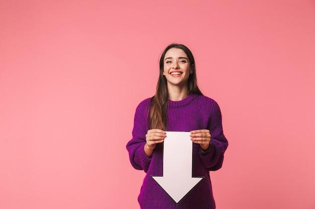 Mooi jong meisje dat trui draagt die zich geïsoleerd over roze bevindt, met een pijl omlaag wijst op exemplaarruimte