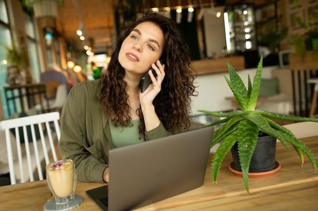 Mooi jong meisje dat werkt in een coffeeshop met een laptopvrouwelijke freelancer die een telefoon vasthoudt die via een computer verbinding maakt met internet en online winkelen doet
