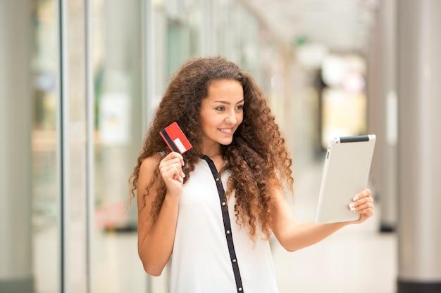 Mooi jong meisje die met creditcard betalen om te winkelen