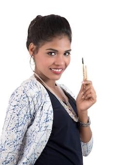 Mooi jong meisje die met make-upborstels genieten die op wit worden geïsoleerd