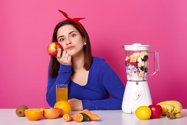 Mooi jong meisje draagt blauwe trui en met rode haarband zit aan tafel en denkt na over haar plannen