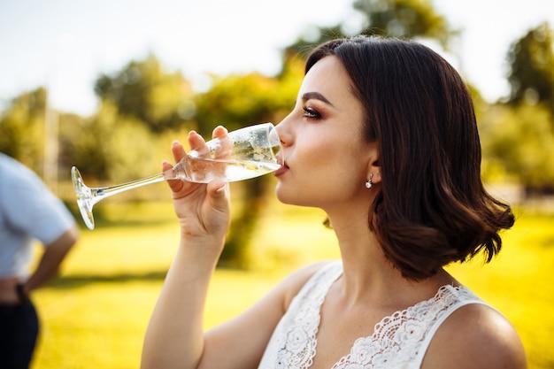 Mooi jong meisje drinkt champagne op een luxe bruiloft.
